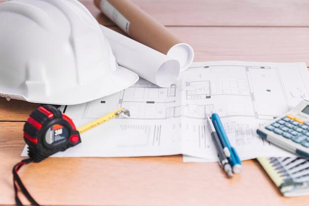 Nahaufnahmehelm und messende werkzeuge auf entwürfen