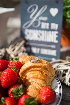 Nahaufnahmehochzeitsringe liegen auf frischen hörnchen, dekorationen an einem hochzeitspicknick mit erdbeeren.