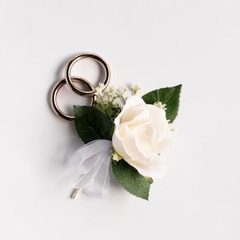 Nahaufnahmehochzeitsringe mit einer rose