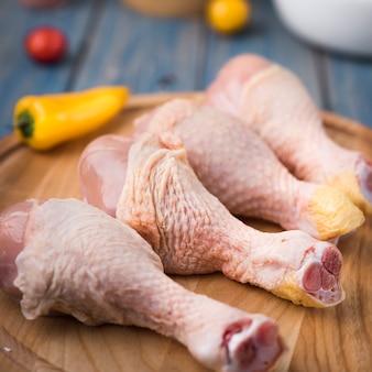Nahaufnahmehühnertrommelstöcke auf hölzernem brett mit pfeffern