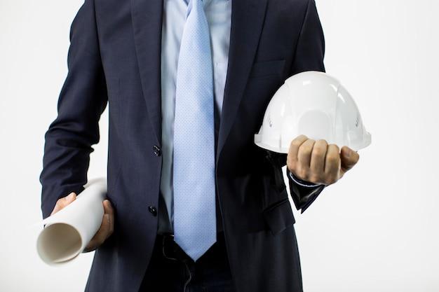 Nahaufnahmeingenieur im formellen anzug hält harten schutzhelmhut und blaupausenrolle