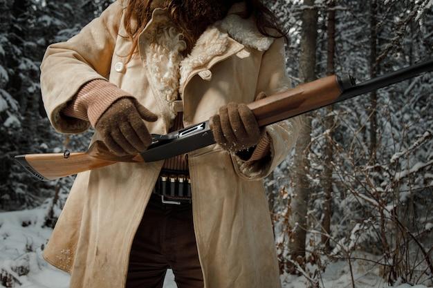 Nahaufnahmejäger in winterweinlesekleidung mit bart im wald mit pistole