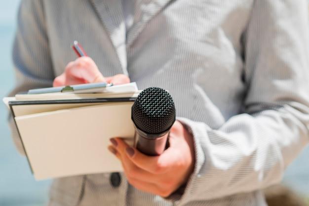 Nahaufnahmejournalistin, die in ihr notizbuch schreibt