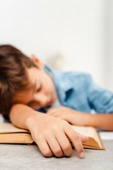 Nahaufnahmejunge, der auf buch schläft