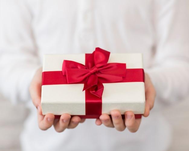 Nahaufnahmejunge, der geschenk hält