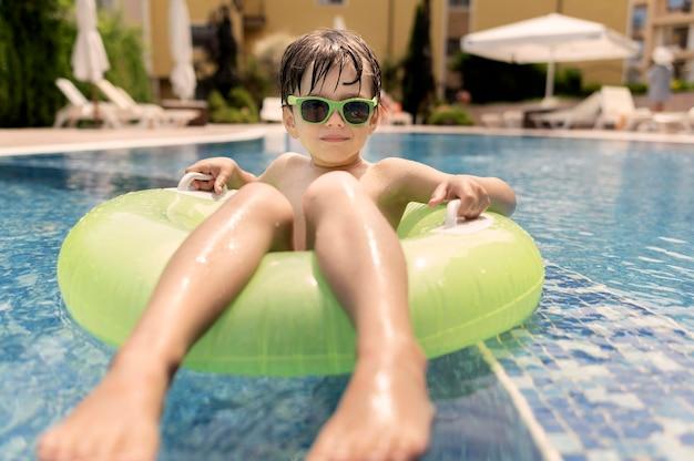 Nahaufnahmejunge im schwimmer am pool