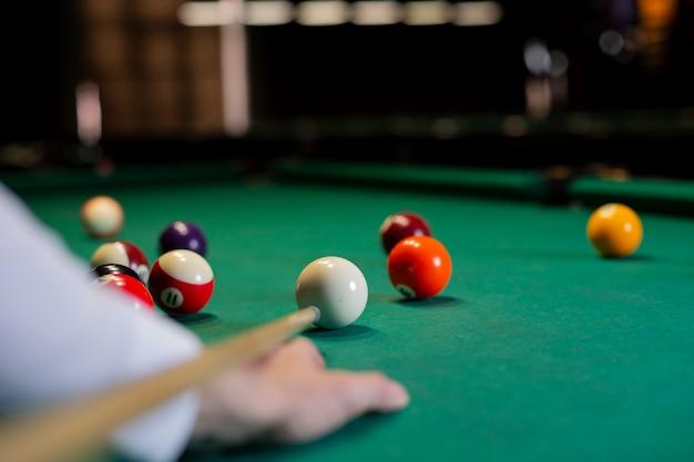 Nahaufnahmejunge mit dem poolstock, der billard spielt