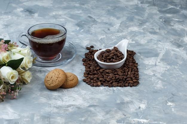 Nahaufnahmekaffeebohnen im weißen porzellankrug mit keksen, tasse kaffee, blumen