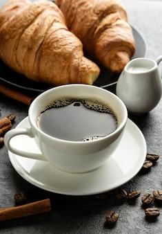 Nahaufnahmekaffeetasse mit croissants und kaffeebohnen