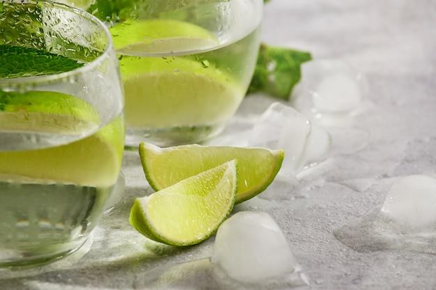 Nahaufnahmekalk- und -minzenwasseralkohol oder nicht alkoholisches getränk. detox wasser. morgenlicht, selektiver fokus. mojito