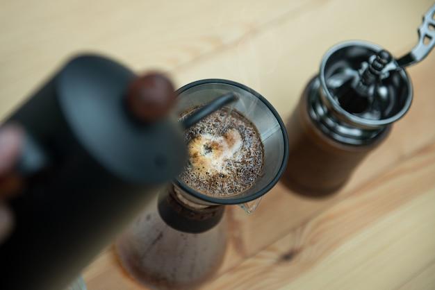 Nahaufnahmekessel, der heißes wasser gießt, um americano-kaffee zu machen