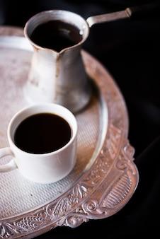 Nahaufnahmekessel und -kaffee auf einer silbernen platte