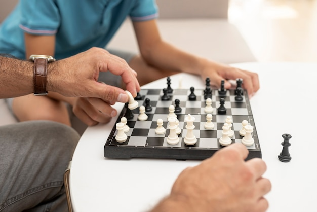 Nahaufnahmekind und -erwachsener, die schach spielen
