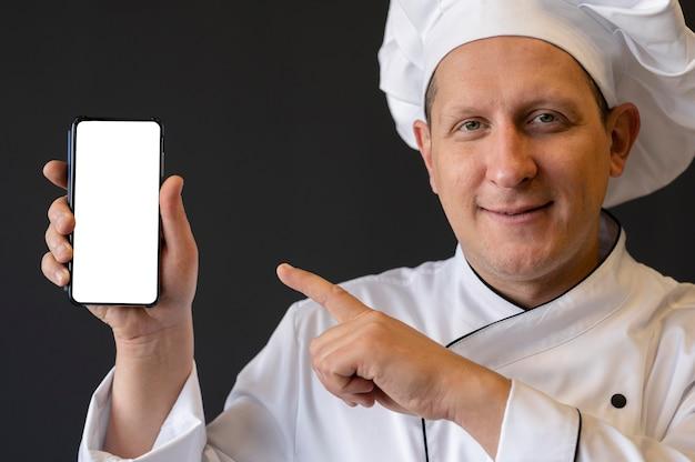 Nahaufnahmekoch, der auf smartphone zeigt
