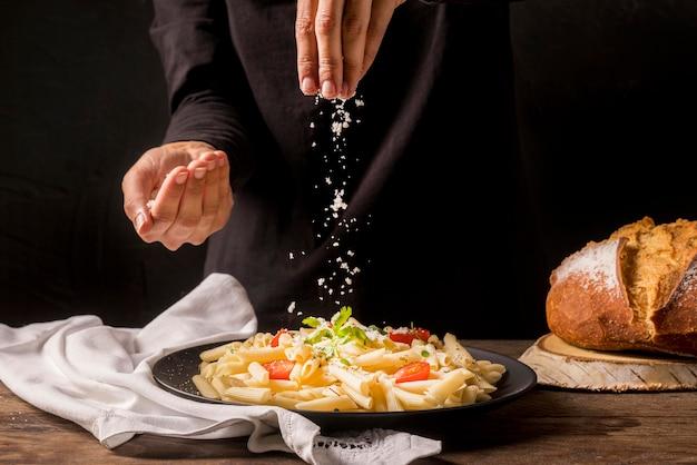 Nahaufnahmekoch, der käse auf nudeln gießt