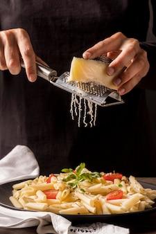 Nahaufnahmekoch, der käse reibt