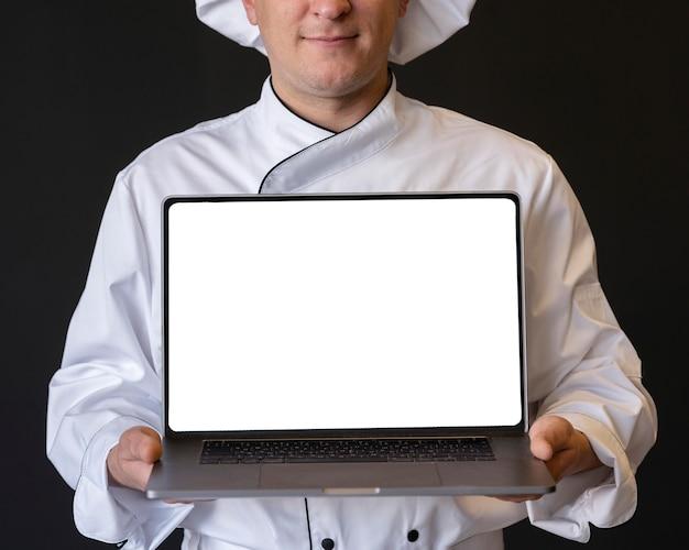 Nahaufnahmekoch, der laptop hält