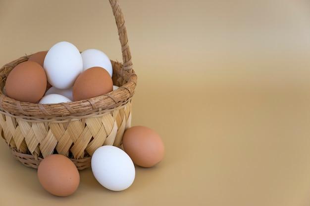 Nahaufnahmekorb mit weißen und braunen eiern auf pastellbeigem hintergrund. bio-hühnereier. frohe ostern.