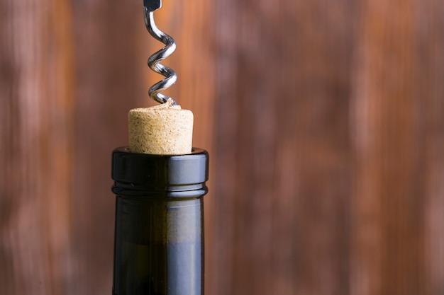 Nahaufnahmekorkenzieher und kopf der weinflasche mit kopienraum