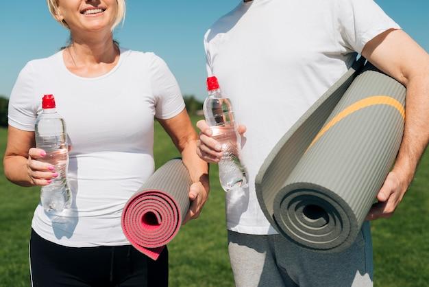 Nahaufnahmeleute, die yogamatten halten