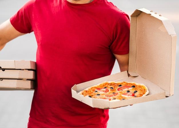 Nahaufnahmelieferant, der pizza hält