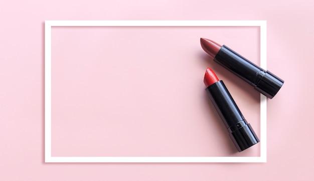 Nahaufnahmelippenstift auf rosa hintergrund. über licht und sooftfokus
