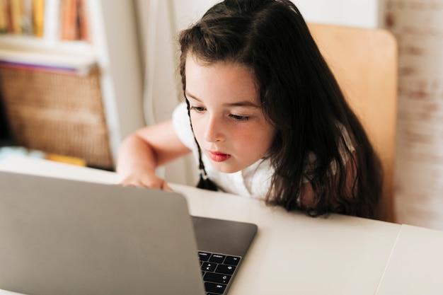 Nahaufnahmemädchen, das auf ihren laptop achtet