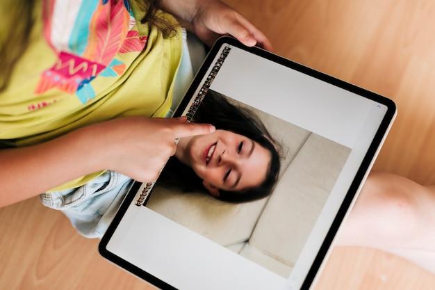 Nahaufnahmemädchen, das fotos auf tablette betrachtet