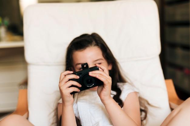 Nahaufnahmemädchen, das fotos mit kamera macht
