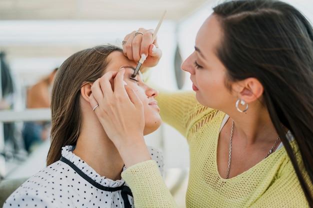 Nahaufnahmemädchen, das make-up vom freund erhält