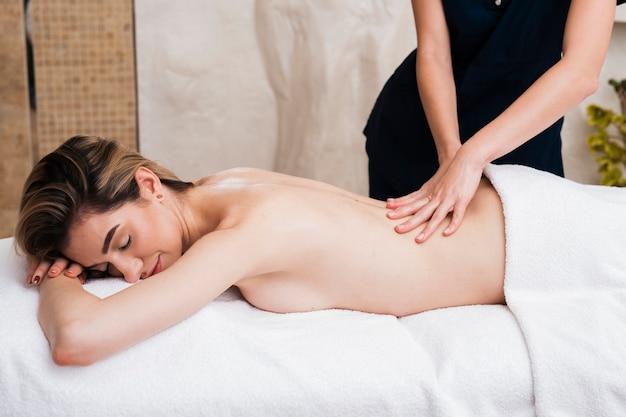 Nahaufnahmemädchen, das mit einer massage sich entspannt
