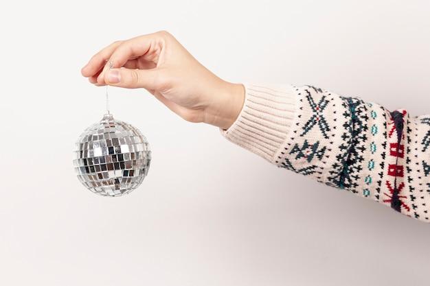 Nahaufnahmemädchen, das weihnachtskugel hält