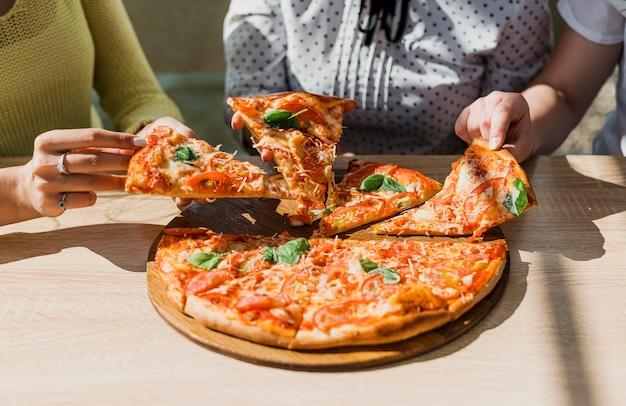 Nahaufnahmemädchen mit pizza am restaurant