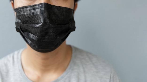 Nahaufnahmemänner, die eine maske tragen, um das coronavirus (covit-19) mit weichzeichner zu schützen