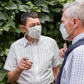 Nahaufnahmemänner, die masken tragen