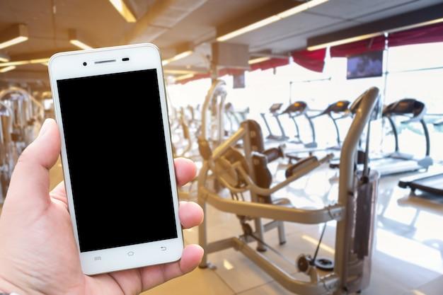Nahaufnahmemänner verwenden hand, die smartphone unscharfe bilder der abstrakten unschärfe des defocused spors hält
