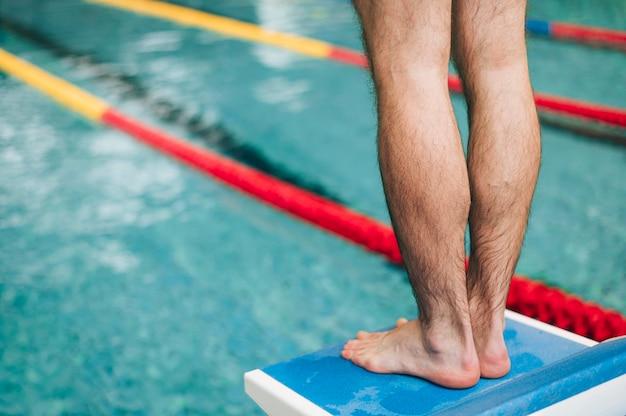 Nahaufnahmemann auf springendem platz am swimmingpool