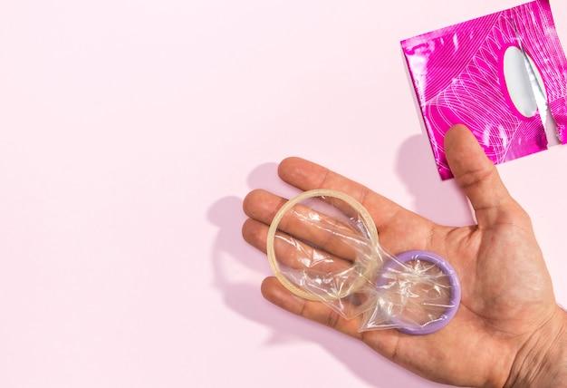 Nahaufnahmemann, der ausgepackte kondome hält