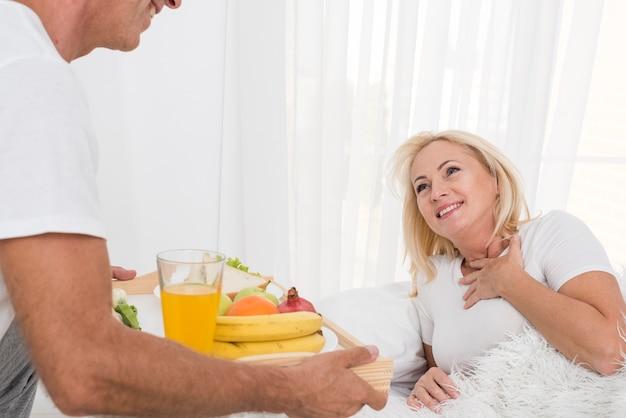 Nahaufnahmemann, der der glücklichen frau frühstück holt