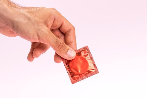 Nahaufnahmemann, der ein eingewickeltes kondom hält