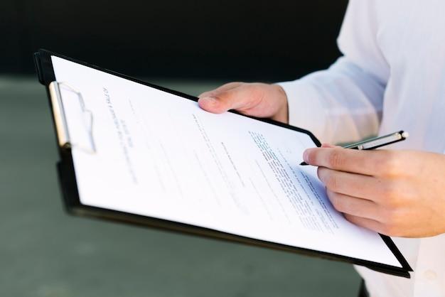Nahaufnahmemann, der einen vertrag unterzeichnet