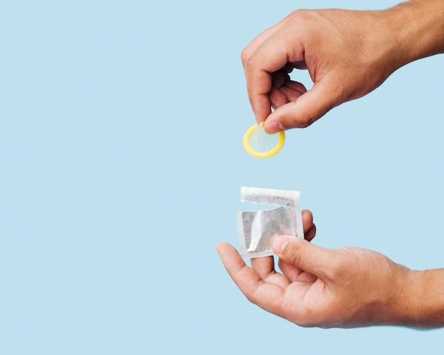 Nahaufnahmemann, der gelbes kondom mit kopieraum hält