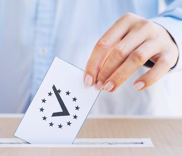 Nahaufnahmemann, der in einen kasten einen stimmzettel einsetzt