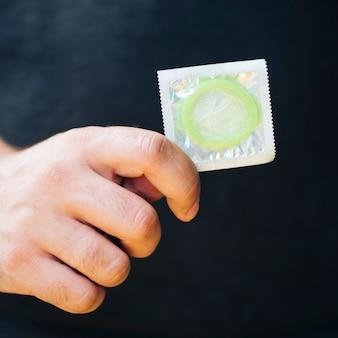 Nahaufnahmemann, der kondom mit schwarzem hintergrund hält