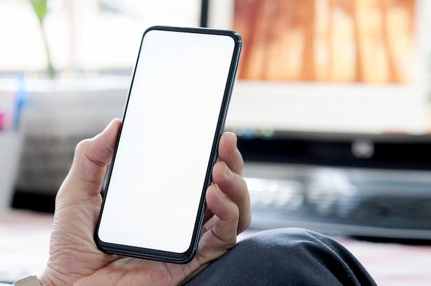 Nahaufnahmemann, der smartphone mit leerem bildschirm beim sitzen am schreibtisch, leerer bildschirm für text verwendet