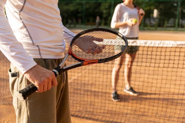 Nahaufnahmemann, der tennisschläger hält