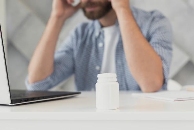 Nahaufnahmemann im büro mit kopfschmerzen