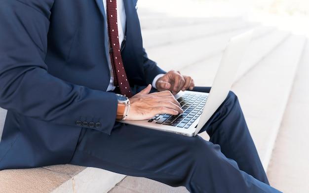 Nahaufnahmemann in der klage, die an laptop arbeitet