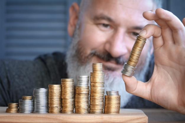 Nahaufnahmemann sammelt spalten von mehrfarbigen münzen von zunehmender höhe.