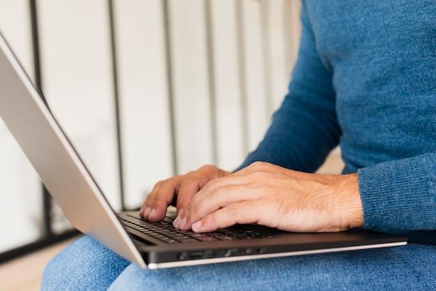 Nahaufnahmemann zu hause, der an laptop arbeitet